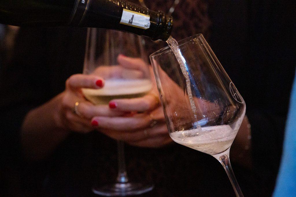Mani che tengono bicchieri di vino pieni